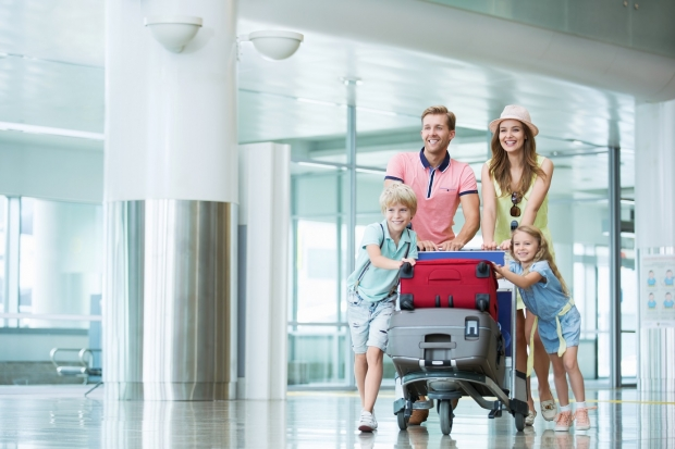 Family pushing a luggage cart in an airport hall