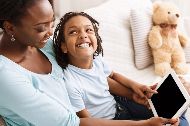 Kid with mom watching tablet