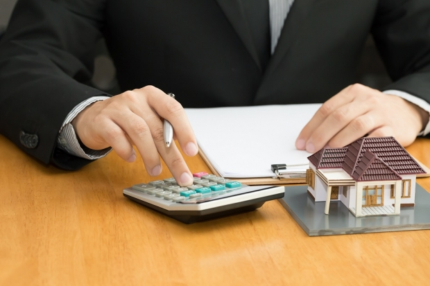 Man using a calculator for his mortgage insurance