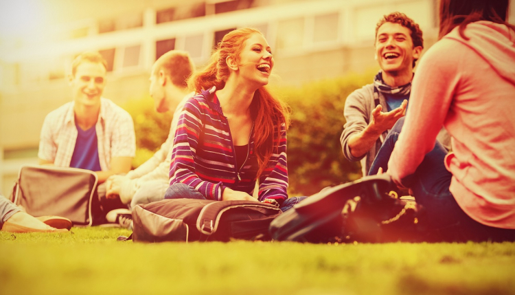 Teenagers sitting outdoors laughing