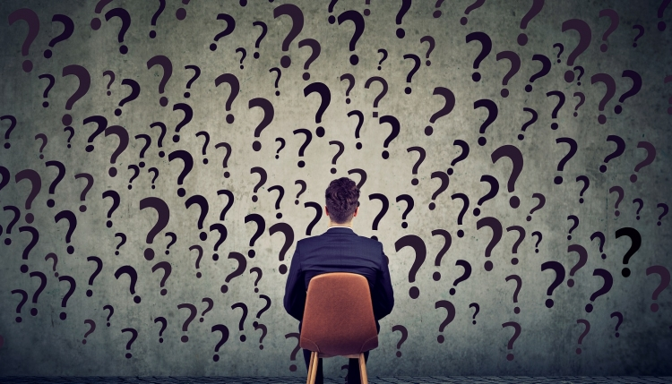 man sitting in front of a wall of question marks